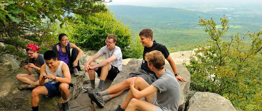 Students relaxing on boulders on a mountain top