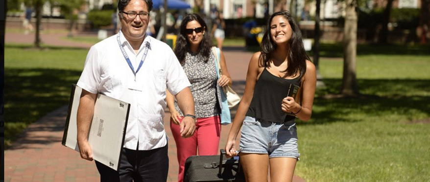 Parents and daughter heading toward dorms for move-in