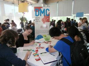 a group of students filling out forms at the DMC table